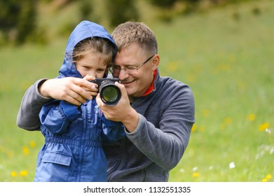 photographer teaching daughter how to use camera in field