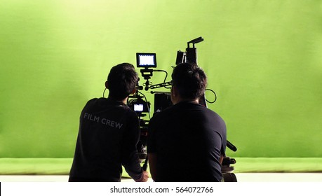 Photographer team and film crew and movie camera and green screen studio.