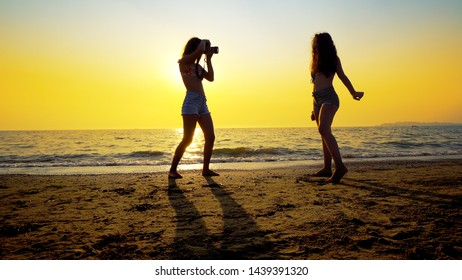Photographer teen taking photos of female model on beach at sunset. Romantic photo session