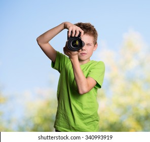 Photographer. Teenage boy using professional camera outdoors