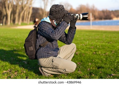Photographer with tele lens making photo. Outdoor