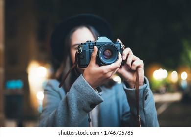 Photographer tourist girl with retro camera take photo on background bokeh light in evening city, Blogger photoshoot photo hobby