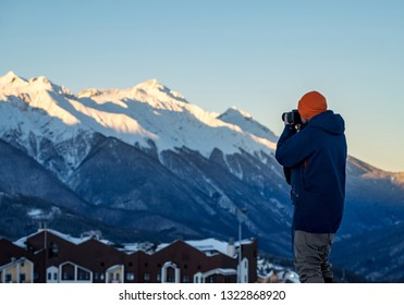 Photographer traveler with camera takes pictures of the snowy mountains in early morning at dawn on winter resort of Krasnaya Polyana. Vacations adventure lifestyle