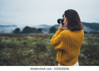 photographer traveler take photo on video camera closeup on background autumn foggy mountain, tourist shooting nature mist landscape outdoor, hobby concept copy space mockup