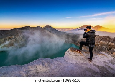 Photographer or Traveller is shooting picture on top of the crater of Kawah Ijen volcano, Indonesia. Outdoors travel concept.