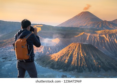 Photographer or Traveller using a professional DSLR camera take photo beautiful landscape of Mount Bromo volcano with sunrise colorful sky, Indonesia. - Recreation and outdoor travel concept.