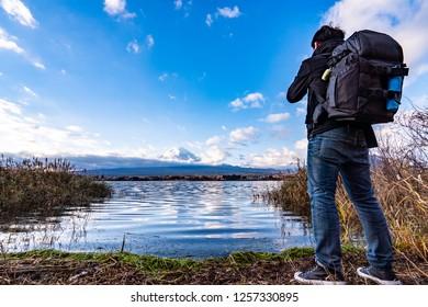 Photographer or Traveller using a professional DSLR camera take photo beautiful landscape of fuji lake at lake kawaguchi, Yamanashi, Japan