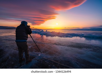 Photographer or Traveller using a professional DSLR camera take photo beautiful landscape of Baikal lake at sunset winter, Rusia - Recreation and outdoor travel concept.