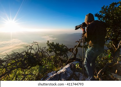 A photographer or traveller using a professional DSLR camera on a tripod in the nature for background.