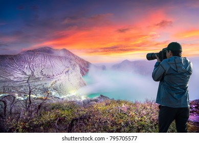 Photographer or Traveller using a professional DSLR camera take photo landscape of Kawah Ijen at Sunrise. The most famous tourist attraction in Indonesia -Recreation and outdoor travel concept.