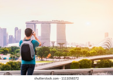 Photographer or traveller using smart phone camera take photo landscape of singapore city with sunset sky, the most famous tourist in Singapore City, Singapore
