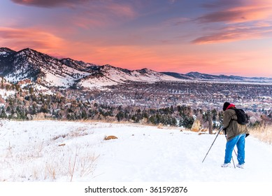 Photographer with a tripod during the winter a sunrise near Boulder, Colorado in the mountains.