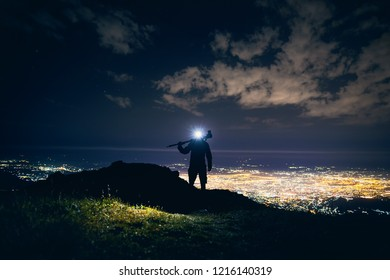 Photographer with tripod in silhouette walking at the mountains with bright Led light against night sky with stars and glowing city light background.