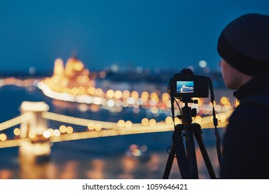 Photographer with tripod. Young man taking photo with his camera in the night city. Budapest, Hungary.