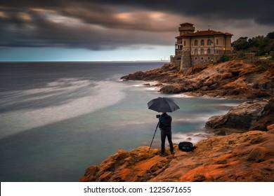 Photographer with umbrella at Boccale Castle on rocky coastline near Livorno, Italy