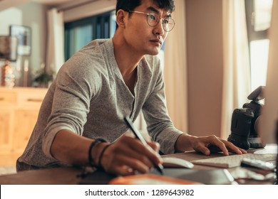 Photographer using a tablet and stylus pen to do photo editing in his studio. Concentrated photo editor working in his studio.