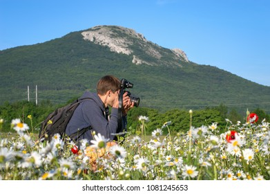 Photographer in the valley takes pictures of the landscape, mountains in the background