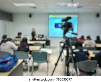 Photographer video recording lecturer and student learning in classroom of university. - E-learning education or smart classroom concept blur image use for background.