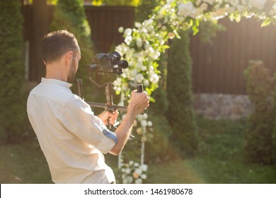 Photographer or videographer shooting wedding ceremony with white and green arch decor on sunset