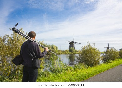 photographer walking with his tripod on the road along the mills in  Kinderdijk, The Netherlands