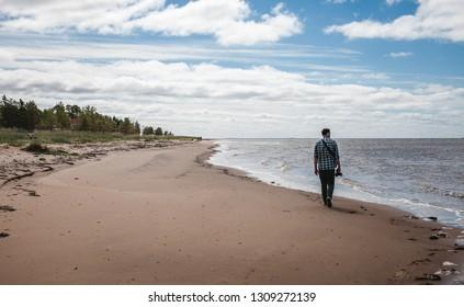 Photographer walks along the coast of the North Sea