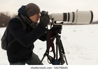 Photographer in winter with big zoom lens on the tripod