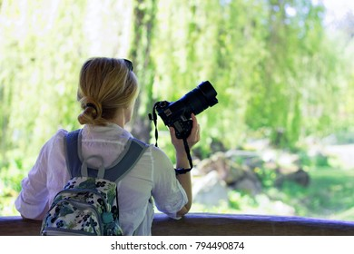 photographer woman is standing and holding a camera, bright garden blurred background. Blond girl with backpack and dslr camera in her hand.