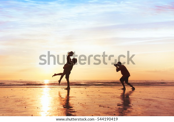 photographer working with couple on the beach, professional wedding photography