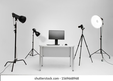 Photographer working place in photo studio with lighting equipment. Camera on the tripod. PC computer on desk. Designer working place.