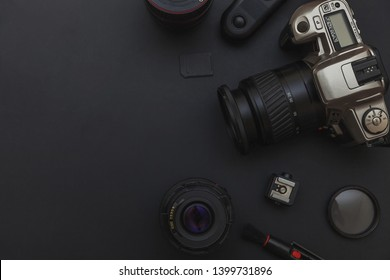 Photographer workplace with dslr camera system, camera cleaning kit, lens and camera accessory on dark black table background. Hobby travel photography concept. Flat lay top view copy space