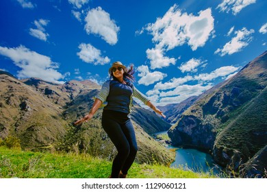 Photographer and young traveler in a relaxing moment jumps outdoors with mountains and rivers in the background. Vacation and lifestyle hiking concept. June 2018, Peru.