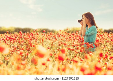 Photographer young woman taking photographs with camera in red poppies field on sunny day.