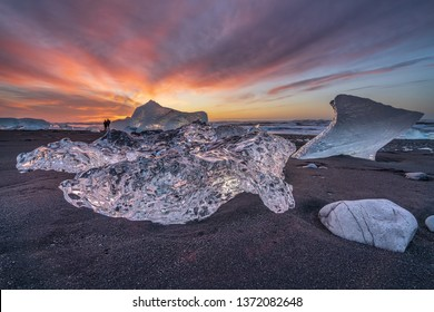 Photographers in the background of big pieces of glacial ice on Diamond beach near Jokulsarlon glacier lagoon in South Iceland