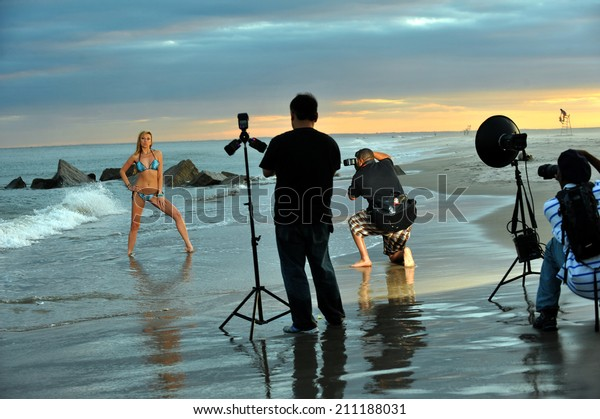 Photographers and bikini model in summer photoshooting on the beach during sunset time.