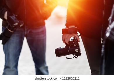 photographers with cameras in backlit - strong sunrays effect in warm colors