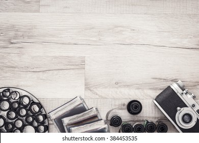 Photographer's desk with negatives, vintage camera and rolls of film. Wooden backdrop. Black and white photography. Top view with copy space.