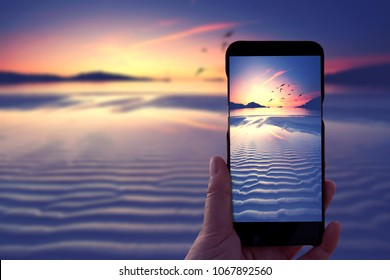 photographers hand holding Smartphone and taking photo of beautiful sunrise at beach