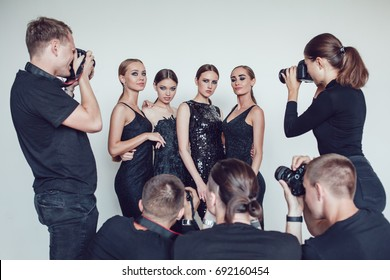 Photographers paparazzi take photos of women in cocktail dresses.