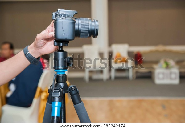 Photographers are saving photos from a camera set on a tripod.