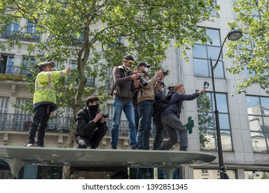 photographers work on top of a bus stop during the May Day protest in Paris, France. 01/05/19
