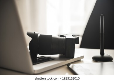 Photographer's workplace with a modern equipment. Mirrorless camera, laptop and graphics tablet.