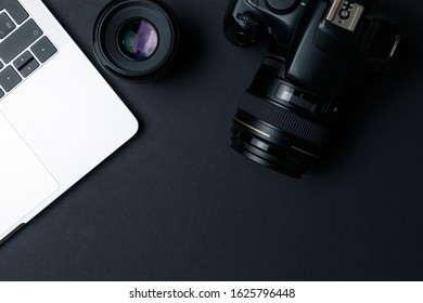 Photographer's workplace on a dark background. Modern laptop, digital camera, lens, battery, smartphone. Minimalism. Top view. Copy space. Equipment for the photographer. The concept of freelancing