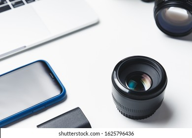 Photographer's workplace on a white background. Modern laptop, digital camera, lens, battery, smartphone. Minimalism. Top view. Copy space. Equipment for the photographer. The concept of freelancing