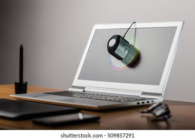 Photographer's workspace with calibrator or profiler attached to laptop's display to get accurate colors