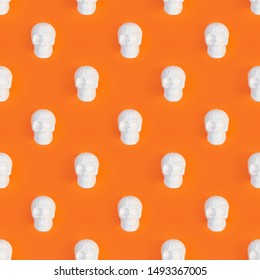 Photographic collage seamless pattern. White human skull toy on orange Halloween background with free space for text top view. Halloween party concept.