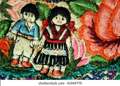 Photographic detail of figures on traditional Guatemalan fabric.