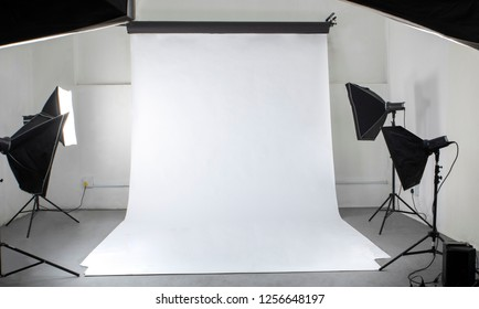 A photographic studio with studio flashes and a white seamless backdrop, from the vantage point of the photographer.