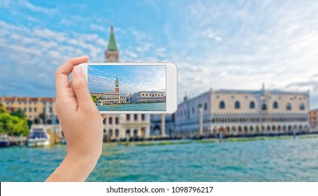Photographing Grand Canal with St.Marks Campanile bell tower on a mobile phone in Venice