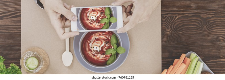 Photographing red soup with cream, basil leaves, and seasoning with a smartphone for a culinary blog