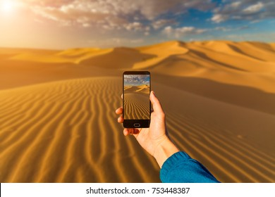 Photographing with smartphone in hand. Travel concept. Sunset in the desert.